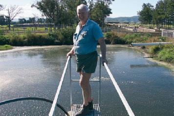 Rod Crawford stands over effluent pond