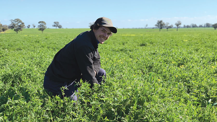 James Harney, farmer from Elmore Compost Crop bends down in field inspecting crop