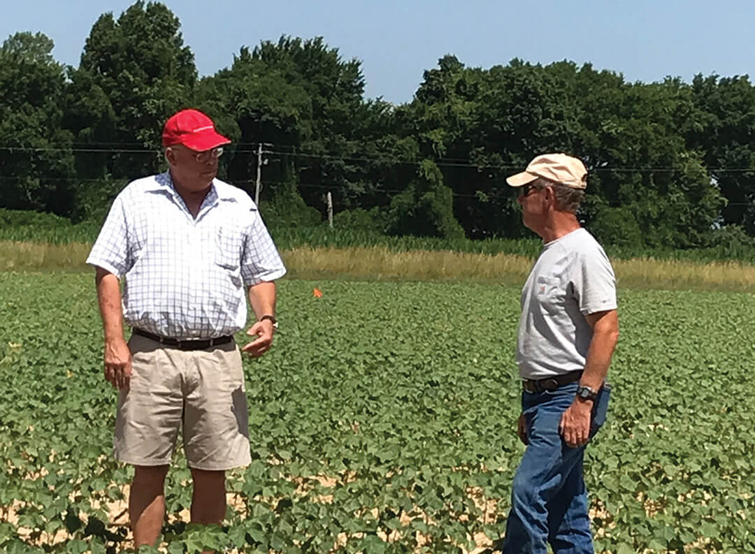 BioAg CEO Anton Barton stands in a field with a grower